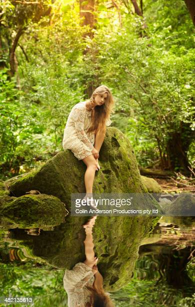 Caucasian woman sitting at edge of creek in woods