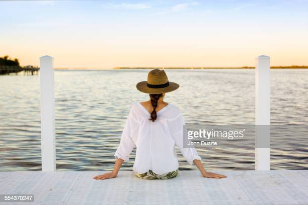 Caucasian woman sitting at edge of pier