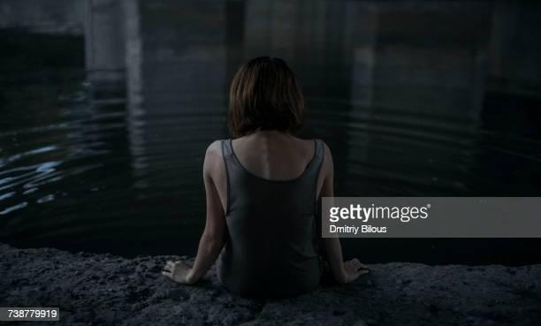 Caucasian woman sitting at edge of water