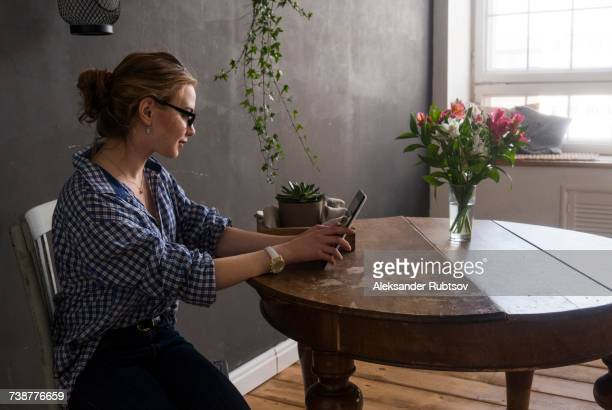 caucasian woman sitting at table using digital tablet - femme russe photos et images de collection