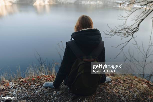 Caucasian woman sitting at the edge of reservoir wearing backpack
