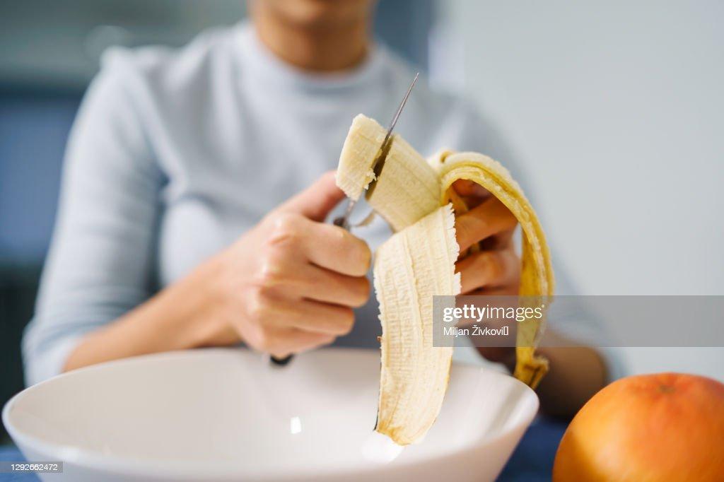 Kaukasische vrouwenzitting door de lijst thuis die banaan snijdt - Volwassen meisje wijfje dat fruitsalade thuis voorbereidt - de ruimte van het gezonde etenconceptexemplaar sluit omhoog : Stockfoto
