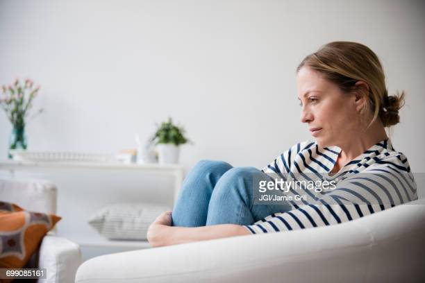 caucasian woman sitting in armchair holding legs - ongerust stockfoto's en -beelden