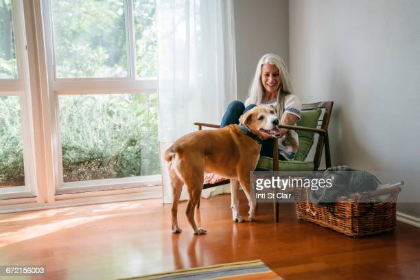 caucasian woman sitting in armchair petting dog - one animal stock pictures, royalty-free photos & images