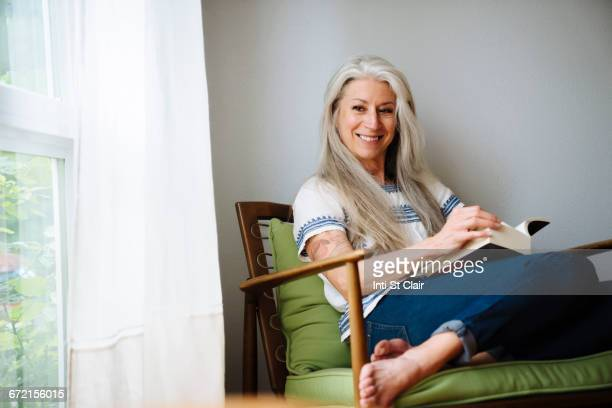 Caucasian woman sitting in armchair reading book