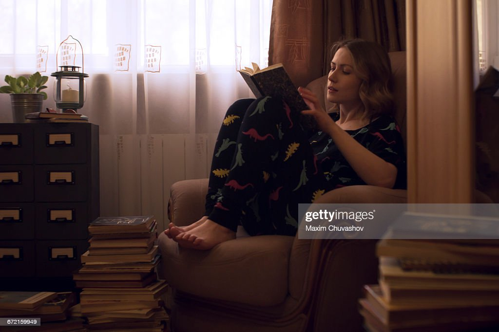 caucasian woman sitting in armchair reading pile of books picture id