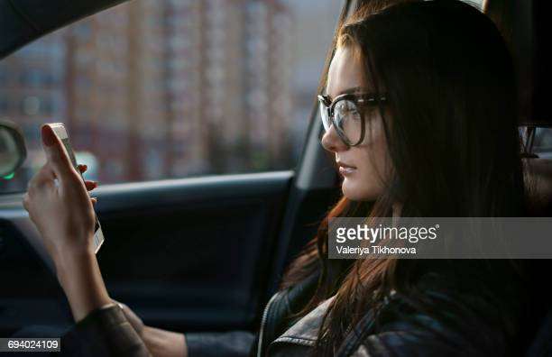 Caucasian woman sitting in car texting on cell phone