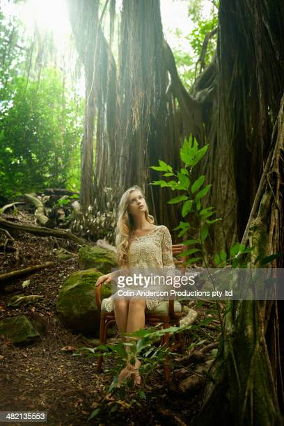 Caucasian woman sitting in chair under banyan tree