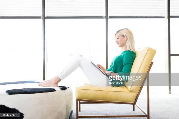 caucasian woman sitting in chair using laptop - ottomane stockfoto's en -beelden