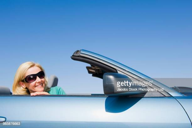 Caucasian woman sitting in convertible under blue sky