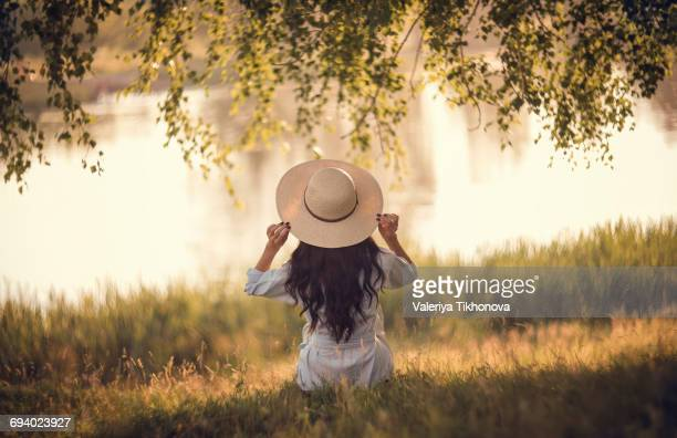 Caucasian woman sitting in grass near river holding hat