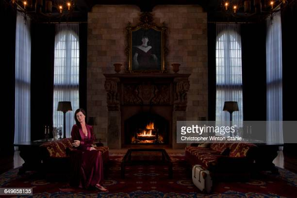 Caucasian woman sitting in ornate living room