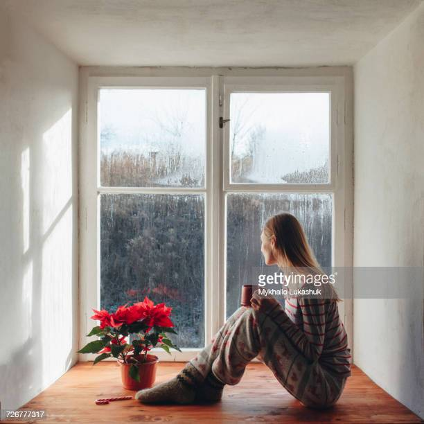 Caucasian woman sitting in window sill drinking coffee in pajamas