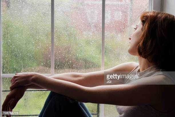 Caucasian woman sitting near rainy window daydreaming