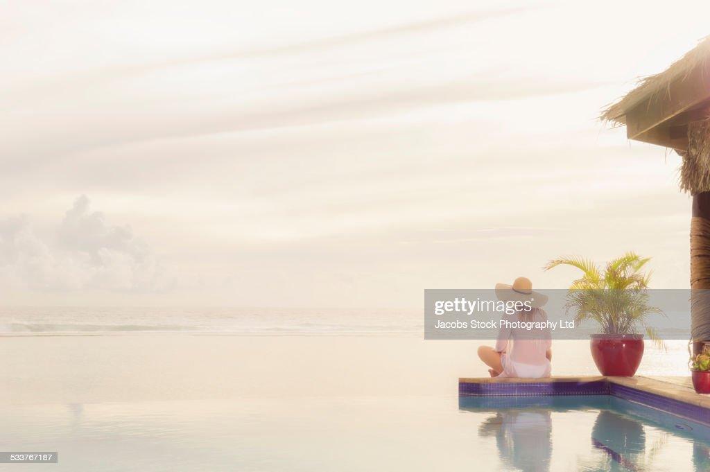 Caucasian woman sitting near swimming pool : Foto stock