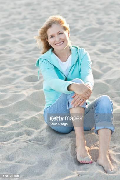 caucasian woman sitting on beach - donne bionde scalze foto e immagini stock