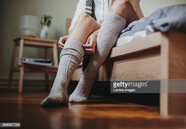 Caucasian woman sitting on bed pulling up socks