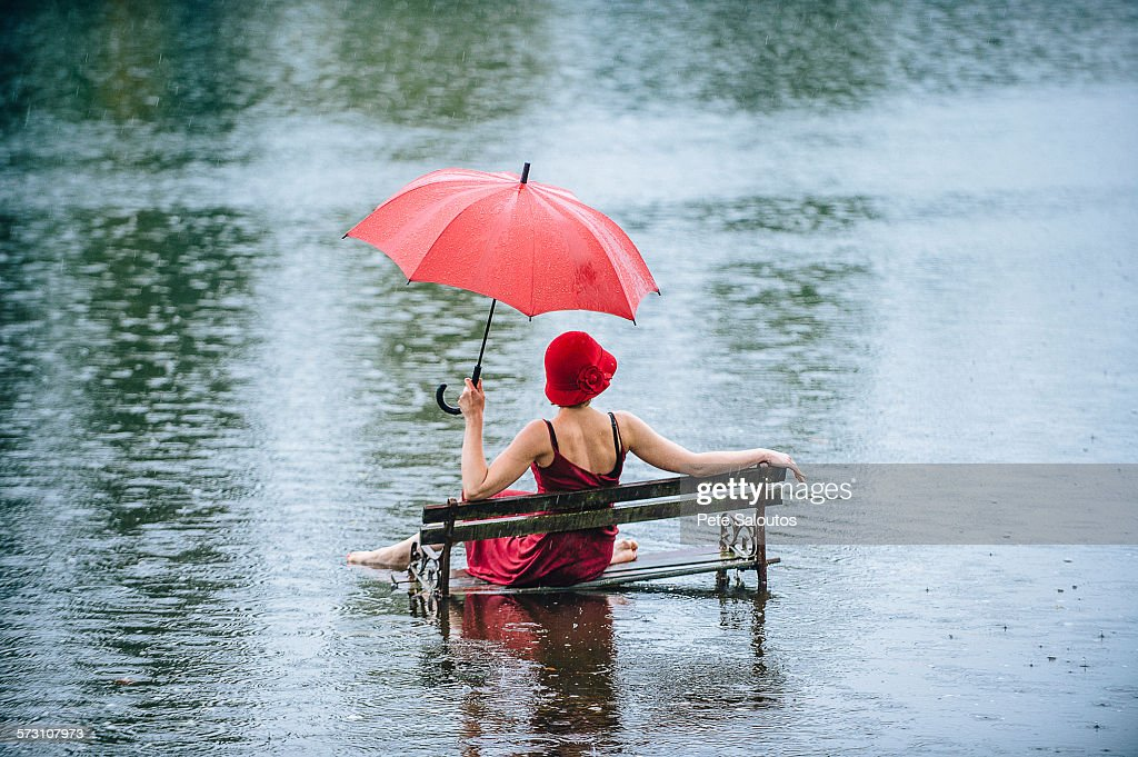 Caucasian woman sitting on bench in flood : Stock Photo