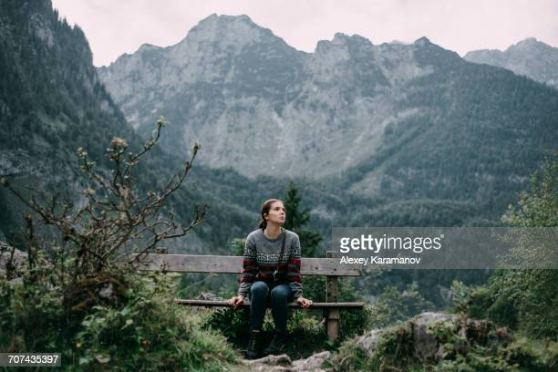 Caucasian woman sitting on bench in mountains