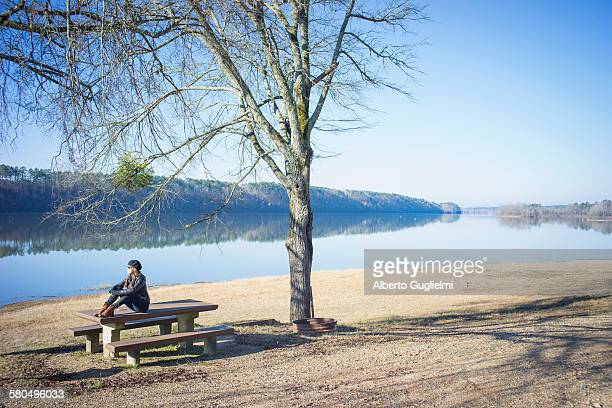 Caucasian woman sitting on bench near rural river