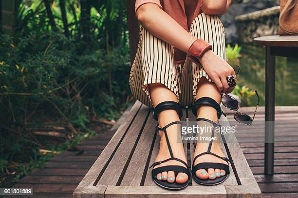 caucasian woman sitting on bench - sandal stock pictures, royalty-free photos & images