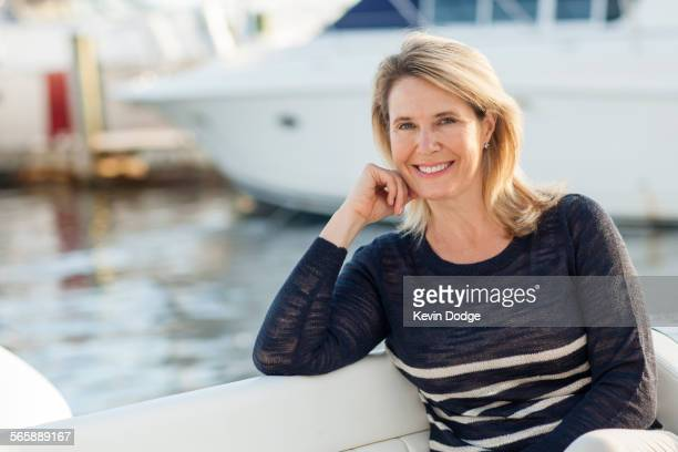 Caucasian woman sitting on boat in harbor
