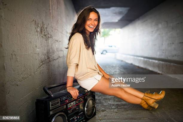Caucasian woman sitting on boom box in tunnel