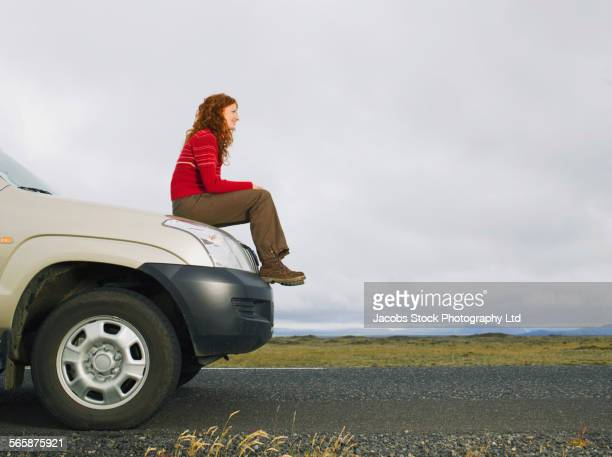 Caucasian woman sitting on car on remote road