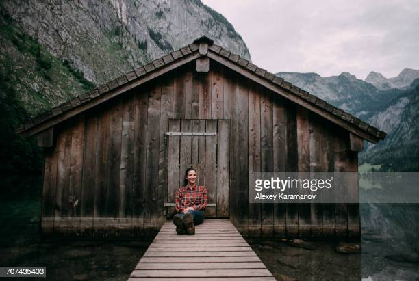 Caucasian woman sitting on dock at remote cabin