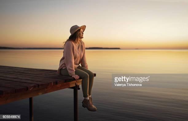 caucasian woman sitting on dock of lake admiring sunset - 桟橋 ストックフォトと画像