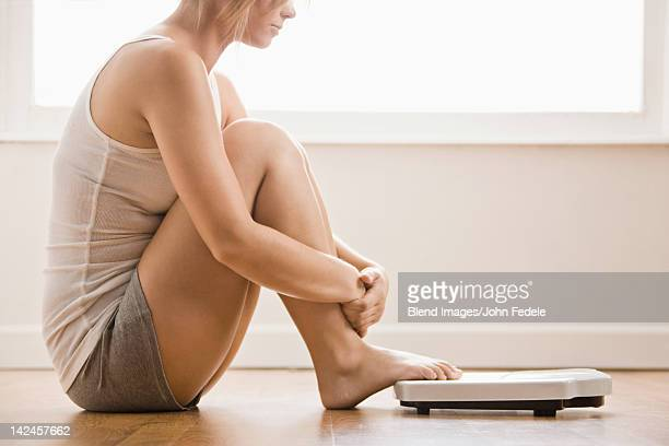 Caucasian woman sitting on floor near scale