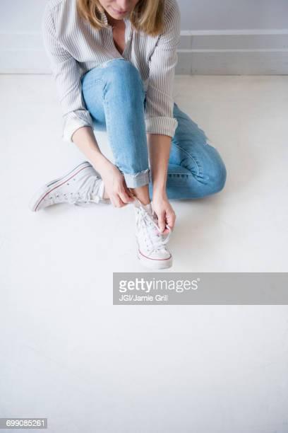 caucasian woman sitting on floor tying shoelace - witte schoen stockfoto's en -beelden
