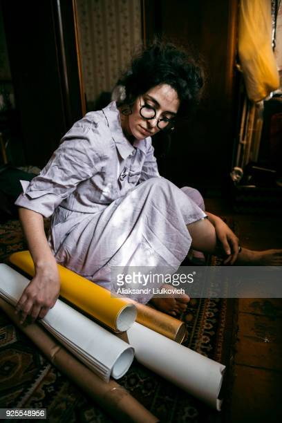 Caucasian woman sitting on floor with rolled up paper