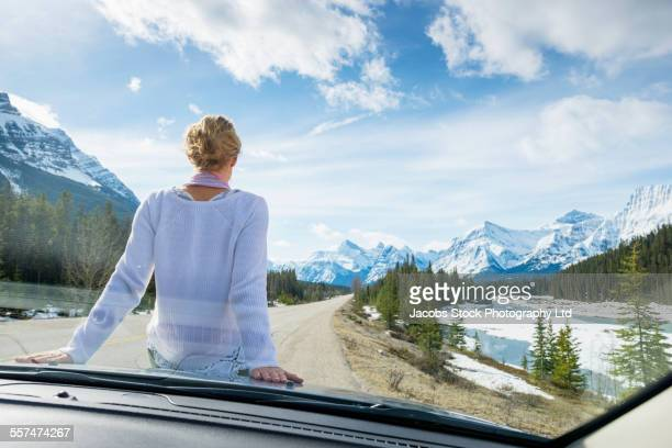 Caucasian woman sitting on hood of car near mountains, Banff, Alberta, Canada