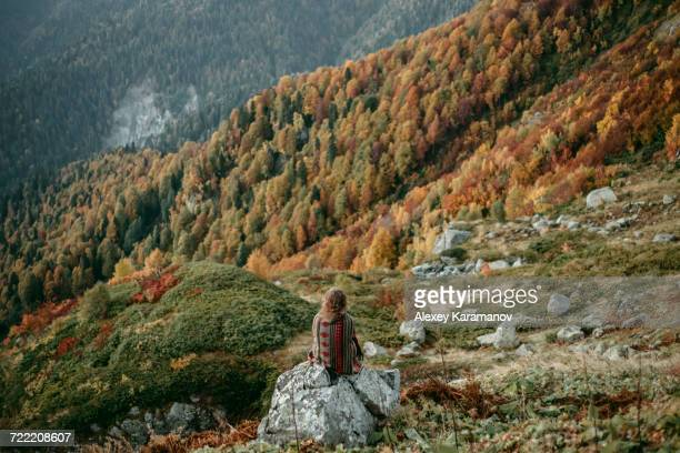Caucasian woman sitting on mountain rock overlooking valley