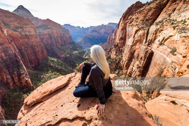 Caucasian woman sitting on rock admiring scenic view of rock formations