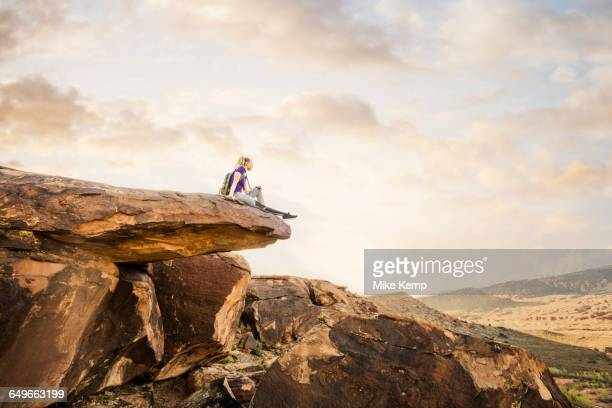 Caucasian woman sitting on rock formation