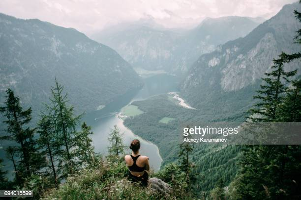 caucasian woman sitting on rock overlooking lake in valley - tal stock-fotos und bilder