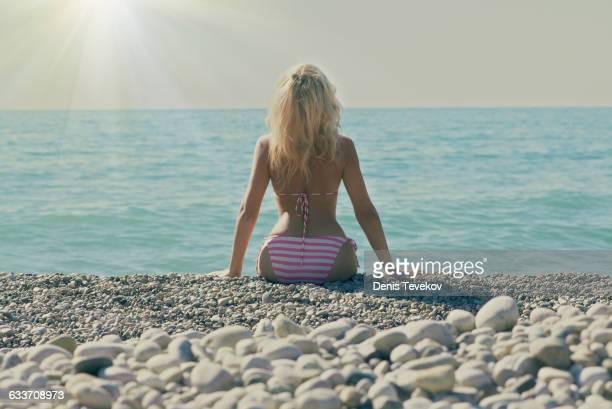caucasian woman sitting on rocky beach - femme blonde en maillot de bain vue de dos photos et images de collection