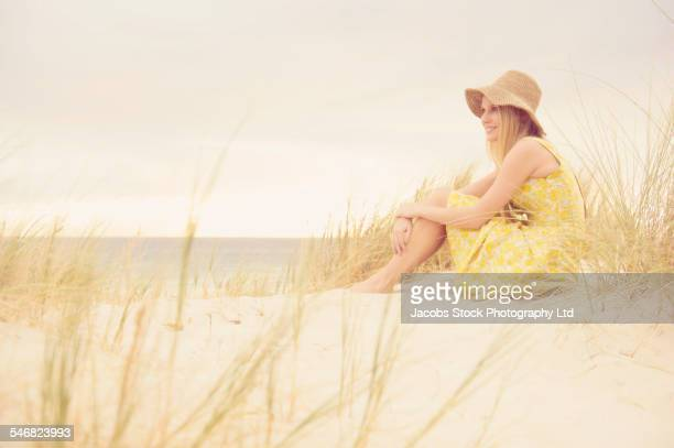 Caucasian woman sitting on sand dune