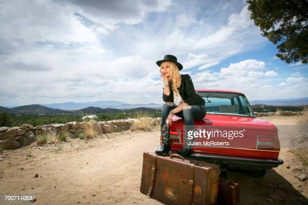caucasian woman sitting on trunk of car with suitcases - woman in broken shoe heel stock pictures, royalty-free photos & images
