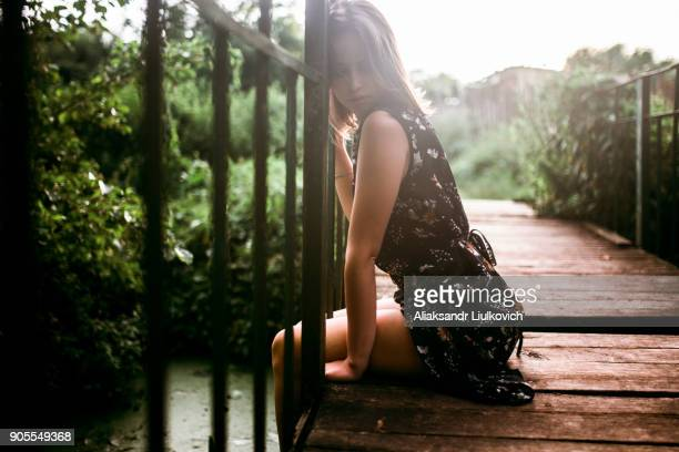 Caucasian woman sitting on wooden bridge