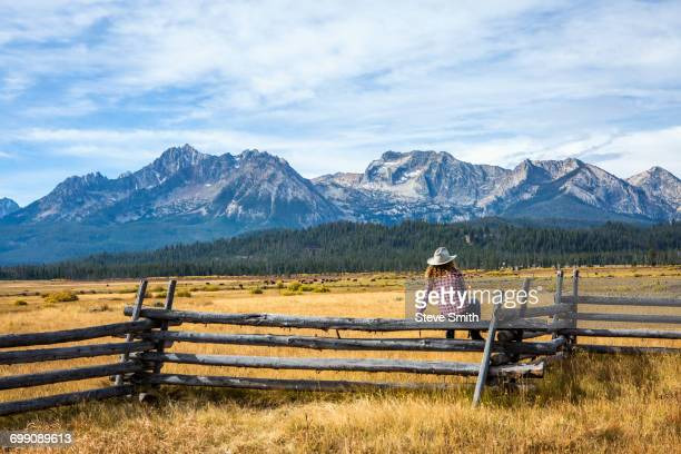 caucasian woman sitting on wooden fence near mountain river - cowgirl hairstyles stock photos and pictures