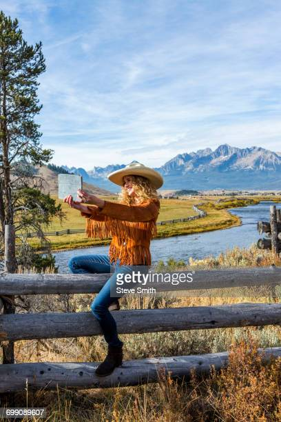 caucasian woman sitting on wooden fence posing for selfie - cowgirl hairstyles stock photos and pictures