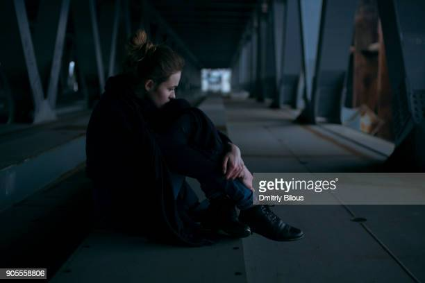 Caucasian woman sitting under bridge