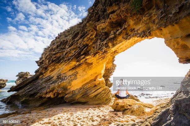 Caucasian woman sitting under rock formation on beach