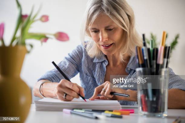 Caucasian woman sketching on pile of paper