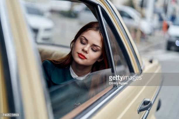 Caucasian woman sleeping in back seat of car