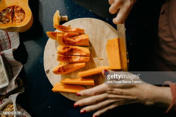 caucasian woman slicing a butternut squash on a wooden cutting board. - chopping stock pictures, royalty-free photos & images