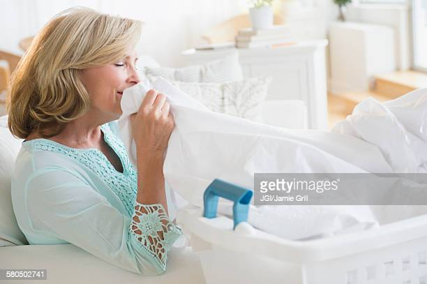 Caucasian woman smelling clean laundry